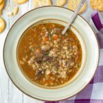 A bowl filled with beef barley soup with a rich and thick broth.