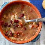 A bowl and spoon with Crock Pot Spicy Bean Soup recipe