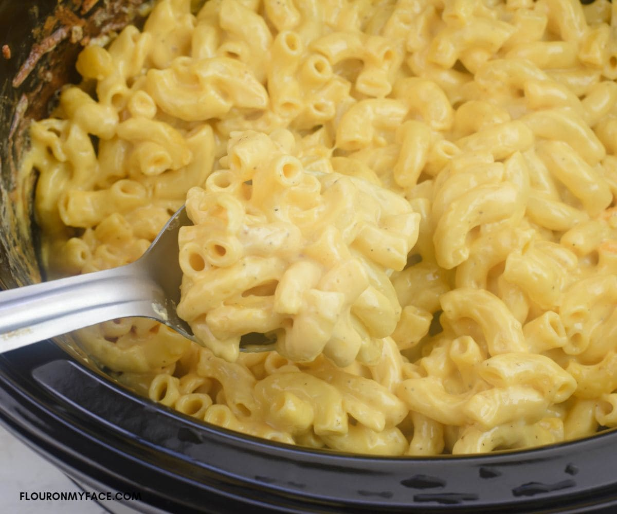 Scooping a serving spoon full of extra creamy macaroni and cheese.
