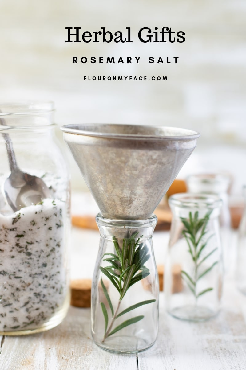 Filling a party favor bottle with rosemary salt to give as gifts during the holidays.