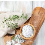 Homemade Rosemary Salt on a wooden cutting board with a fresh rosemary sprig and a tan linen napkin.