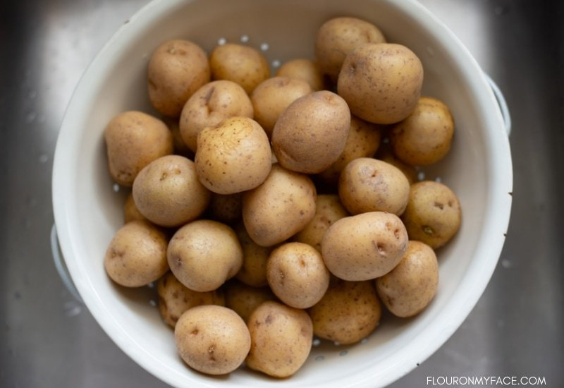 Wash and scrubbed new baby potatoes in a colander in the sink