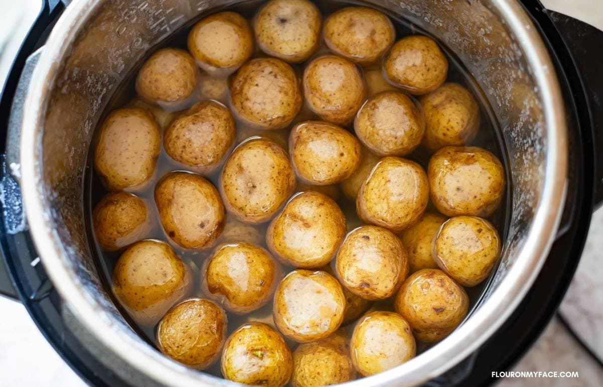 Cooked baby potatoes in the pot of a pressure cooker.