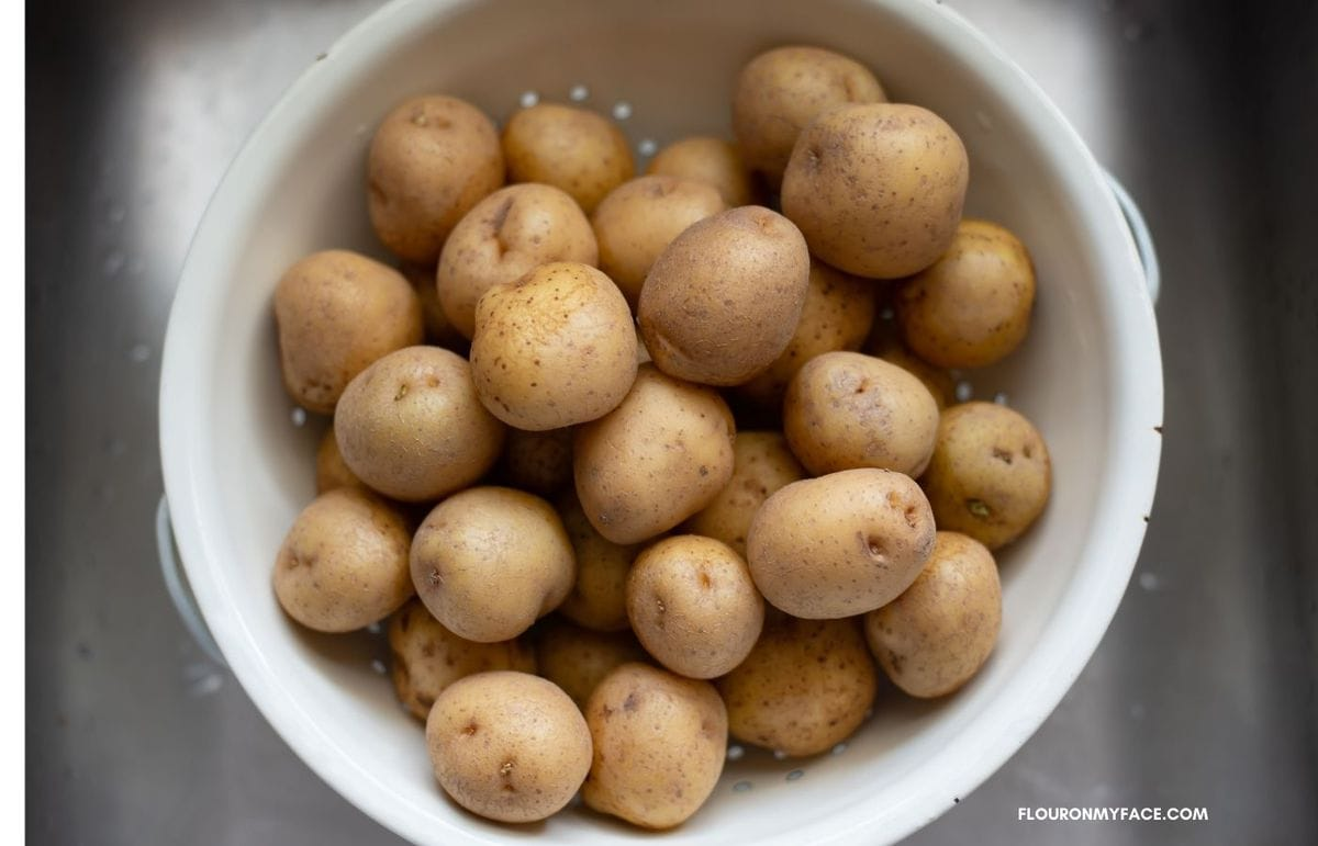 New baby potatoes in a white colander.