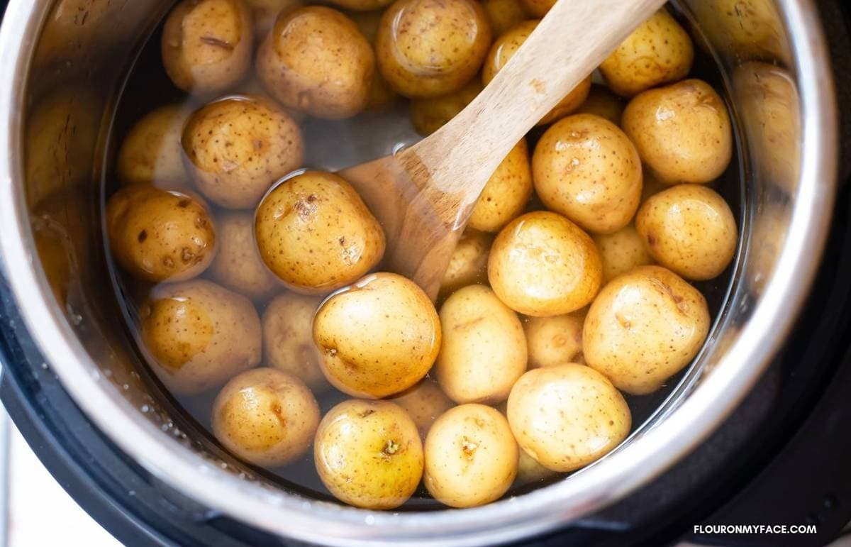 Tossing potatoes in salted water with a spoon.