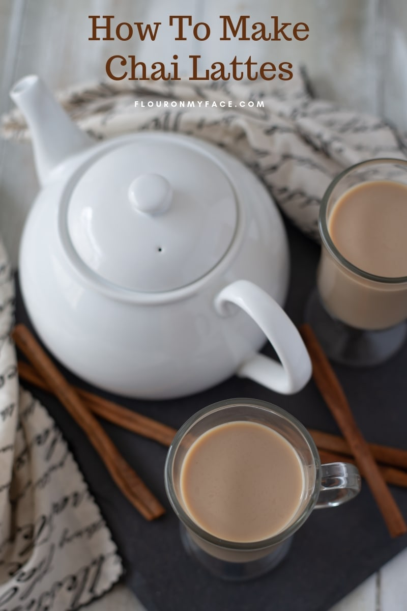Homemade Chai Lattes, with a white tea pot and cinnamon sticks