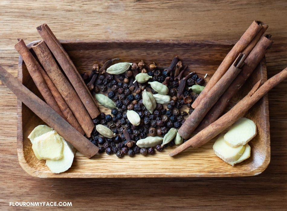 A wooden bowl with cinnamon sticks, peppercorns, cardamon pods, whole cloves and fresh ginger slices. All the spices you need to make a chai tea latte at home