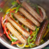 How To Make Instant Pot Brats photo with browned brats and sliced peppers and onions inside the Instant Pot