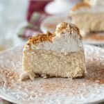 Eggnog cheesecake topped with whipped cream and dusted with cinnamon on a plate.