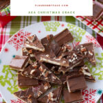 Saltine Cracker Toffee recipe cut into bite size pieces on a red and green Christmas serving plate.