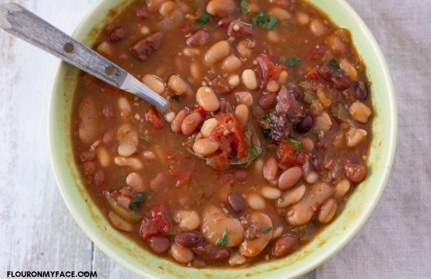 A green vintage bowl with a serving of piping hot Instant Pot Cajun 15 Bean Soup recipe.