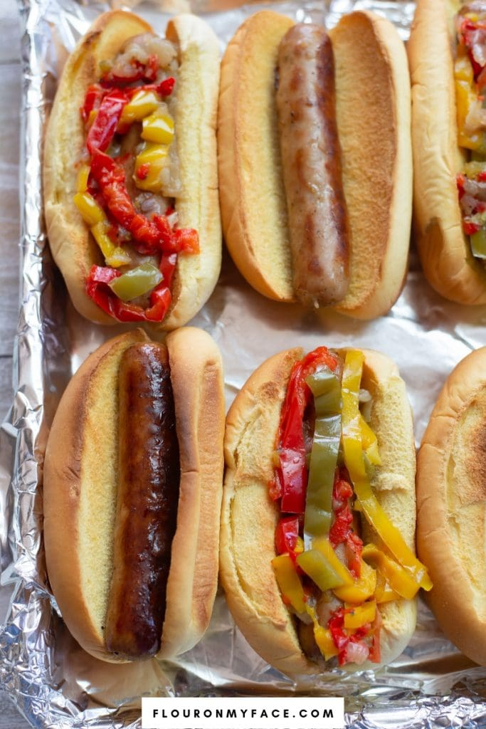 A tray with Instant Pot Brats and Peppers served on Martin's Potato Rolls.