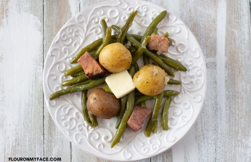 Instant Pot fresh Green Beans and new potatoes cooked with ham and served on a white plate with a pat of melting butter.
