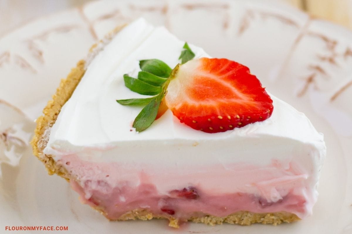 Closeup of a slice of strawberry pie topped with whipped cream.