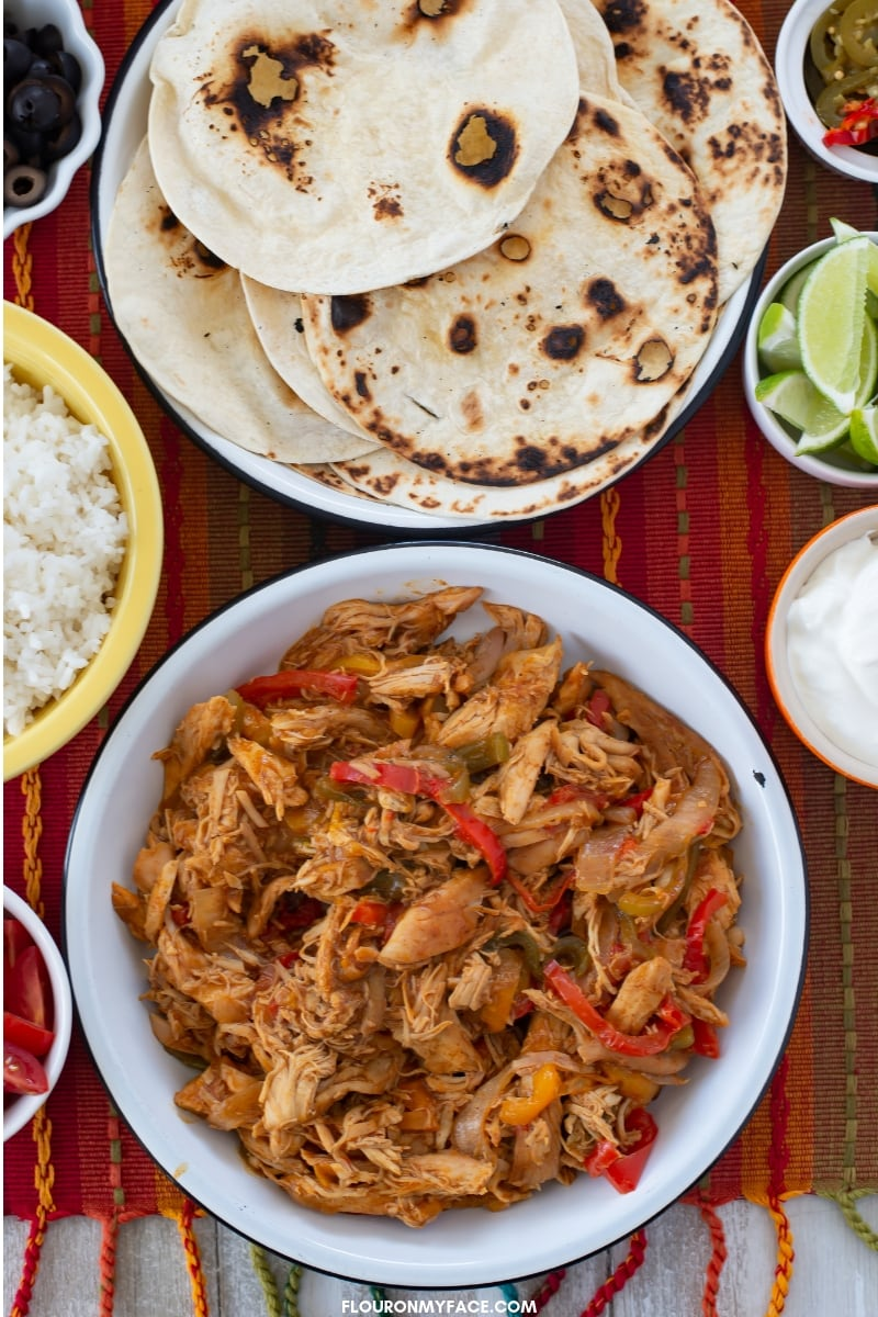 Chicken Fajita fillings, warm flour tortillas, cooked white rice, lime wedges, and sour cream to top chicken fajitas with.