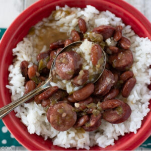 Red Fiestaware bowl with filled with Instant Pot Red Beans and Rice, served with crusty French bread
