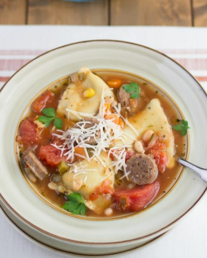 Soup bowl filled with Italian Sausage and cheese ravioli soup.