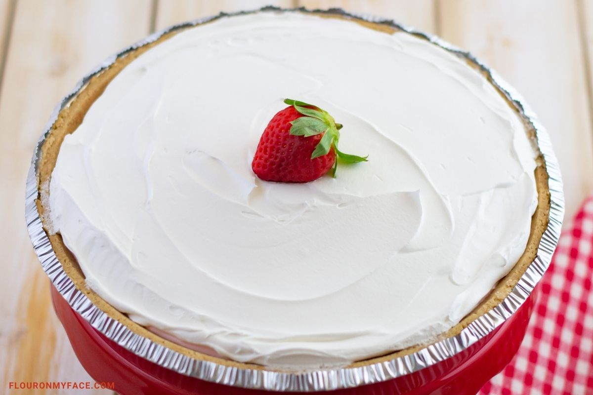 Uncut Strawberry Pudding Pie on a cake stand.