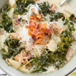 A tan bowl filled with a serving of Crock Pot Zuppa Toscana Soup recipe