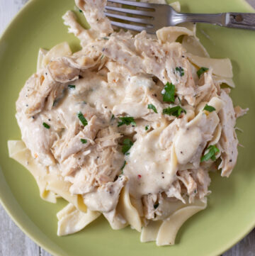 serving crock pot cream cheese chicken over cooked wide egg noodles.