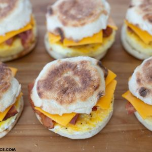 Image of 6 Freezer Breakfast Sandwiches on a wooden cutting board, ready to wrap in plastic wrap and put in the freezer.