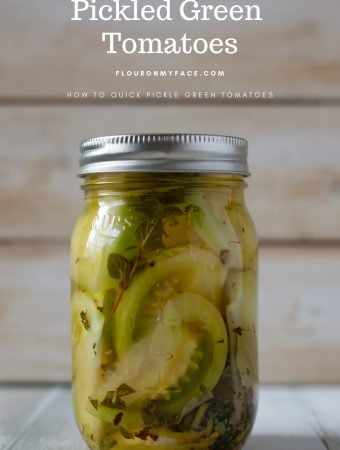 Canning jar full of pickled green tomatoes with herbs, spices and fresh garlic cloves