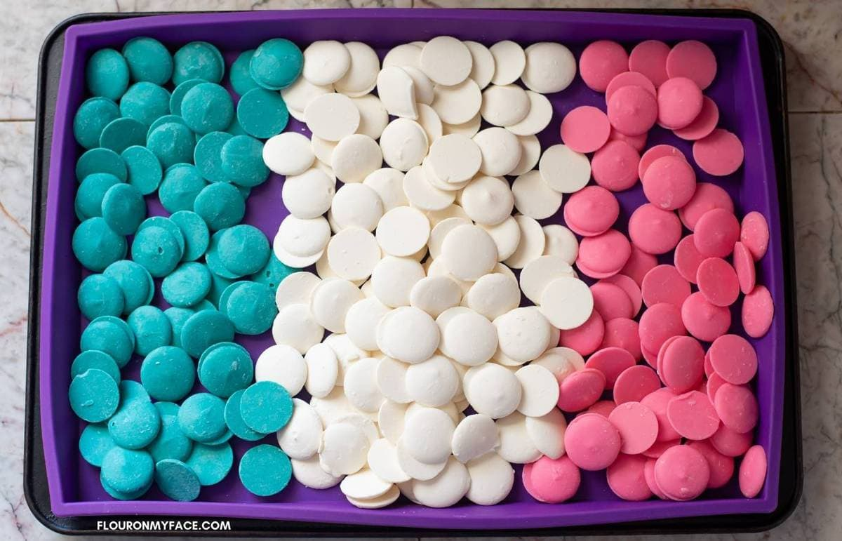 Teal, white and pink candy melts in a rectangle silicon mold.