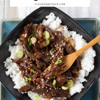 a black and turquios bowl filled white cooked white rice and tender Crock Pot Mongolian Beef