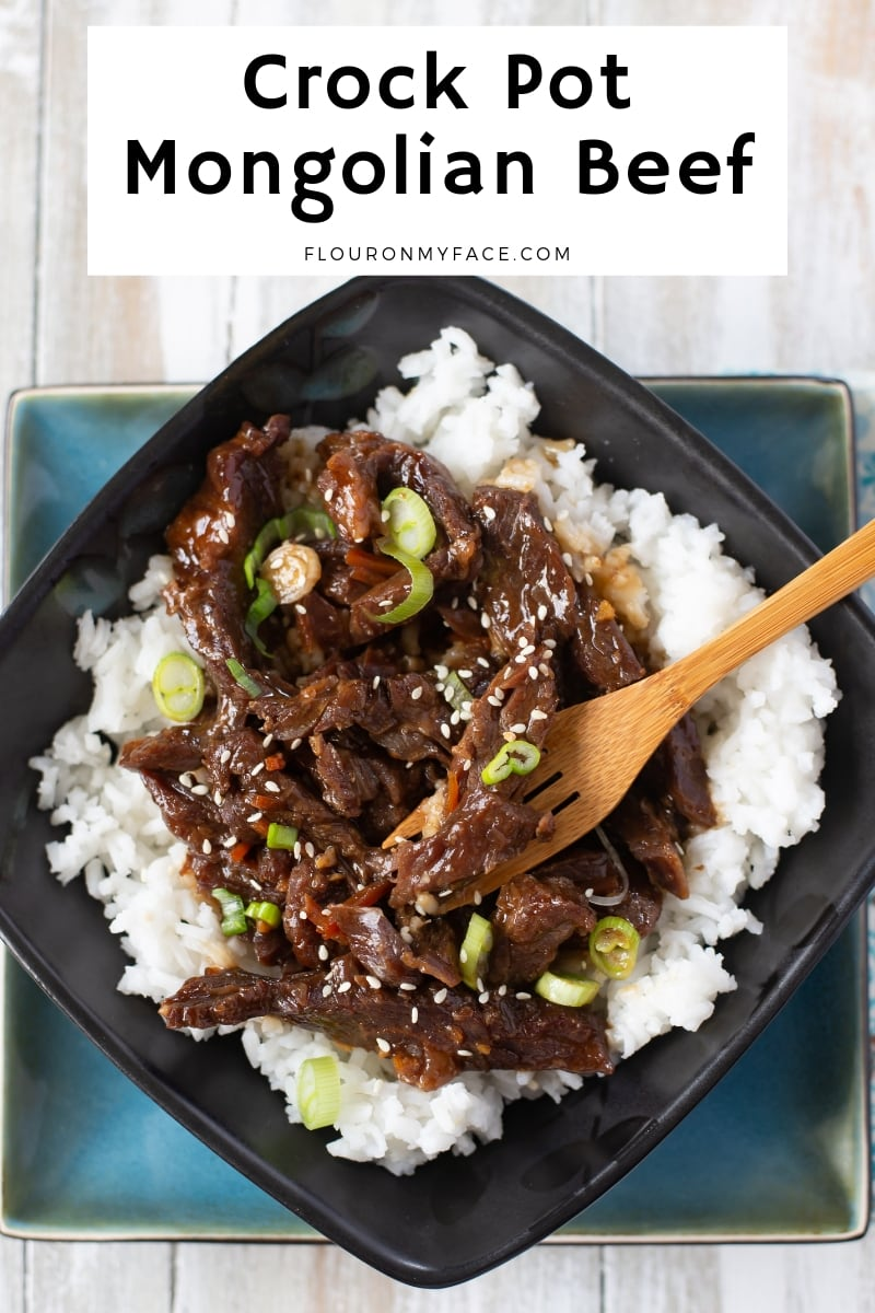 a black and turquoises bowl with a bamboo fork filled with cooked white white rice topped with tender Crock Pot Mongolian Beef for your June Weekly Meal plan and is a perfect summer crock pot recipe