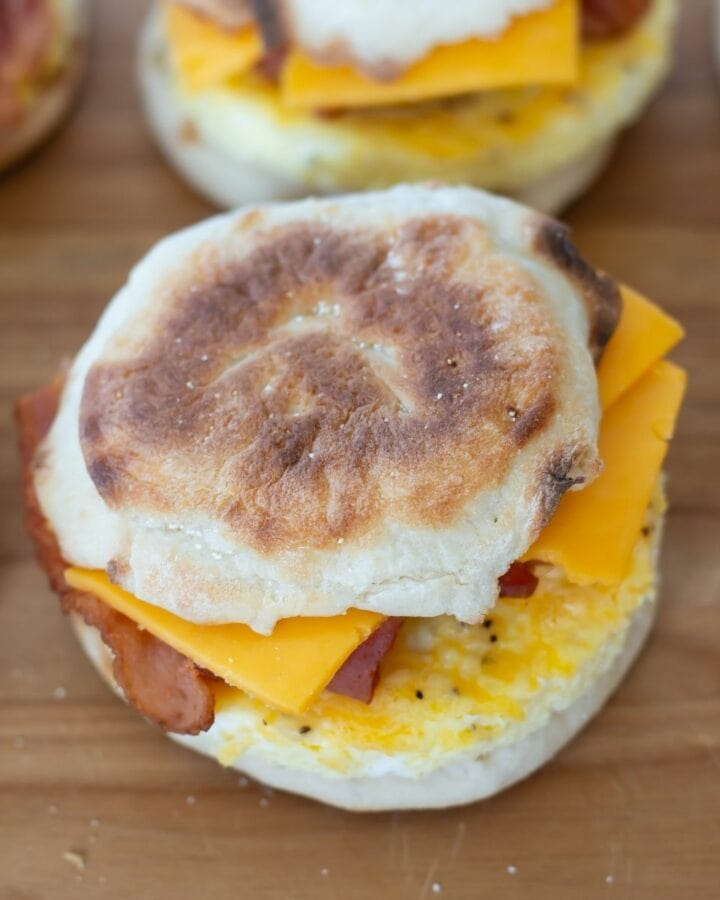 English Muffin Breakfast sandwiches on a wooden cutting board.