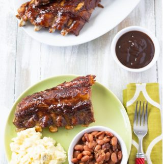 serving Instant Pot Ribs slathered in barbecue sauce with a small bowl of baked beans and a serving of potato salad