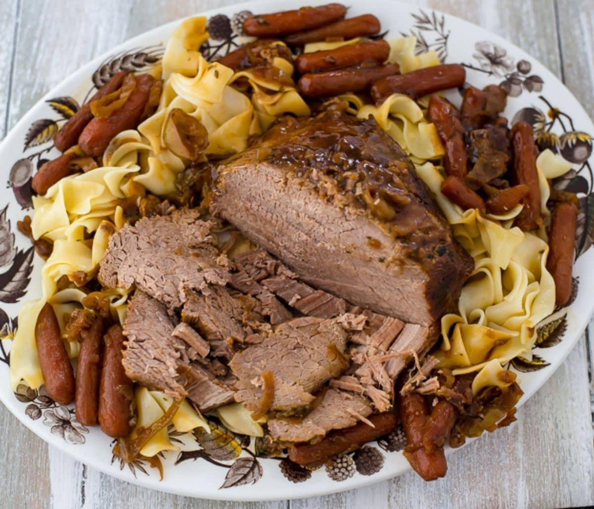 A sliced pot roast on a platter surrounded by noodles and carrots.