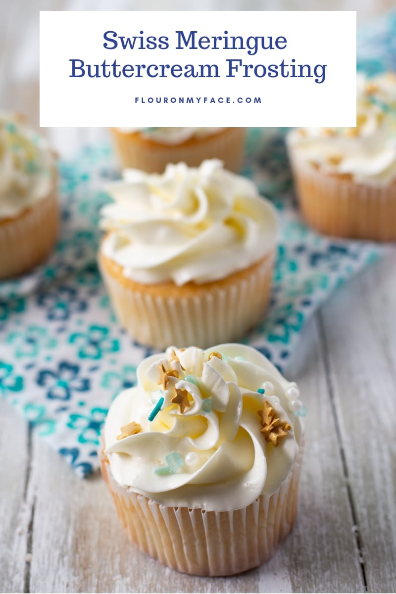 5 Vanilla cupcakes on a teal and blue cloth napkin that have been frosted with Swiss Meringue Butter Cream Frosting