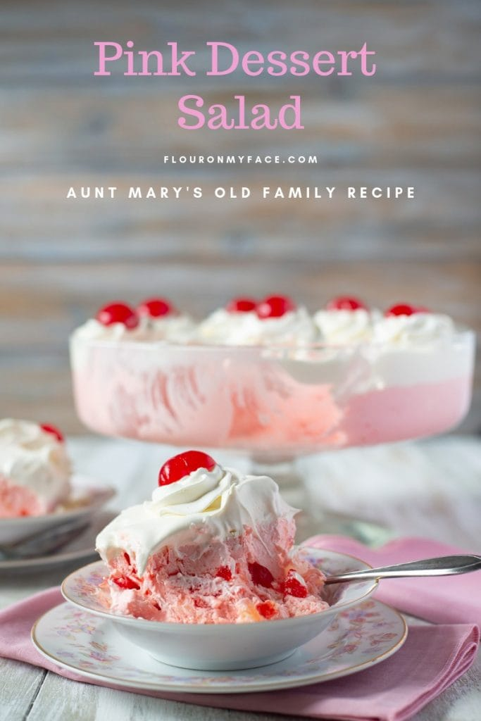 Two servings of Pink Salad on vintage dessert plates with a trifle bowl of the layered pink and white ingredients.