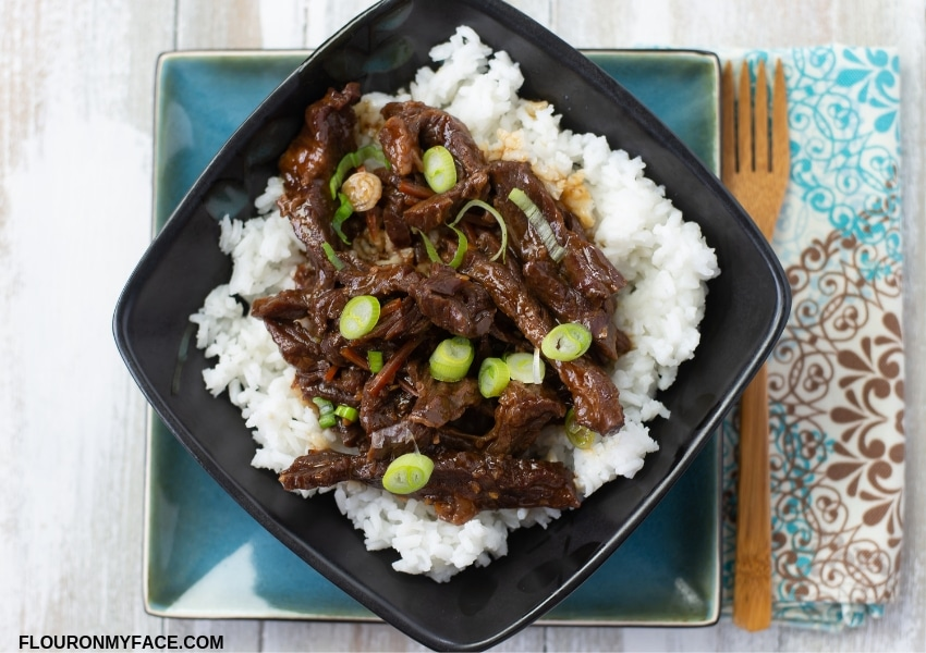 A black glass bowl filled with a serving of crock pot Mongolian Beef served over cooked white rice.
