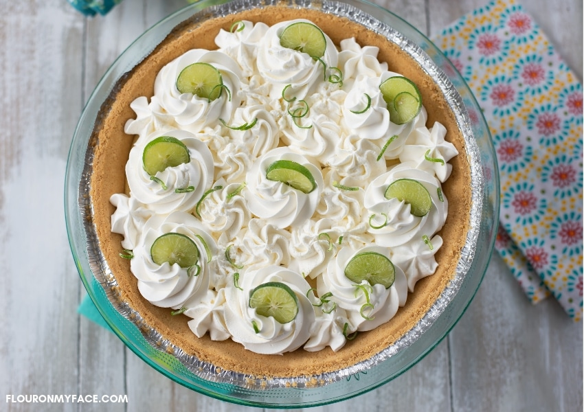 An uncut Key Lime Pie topped with whipped cream rosettes and garnished with Key lime slices