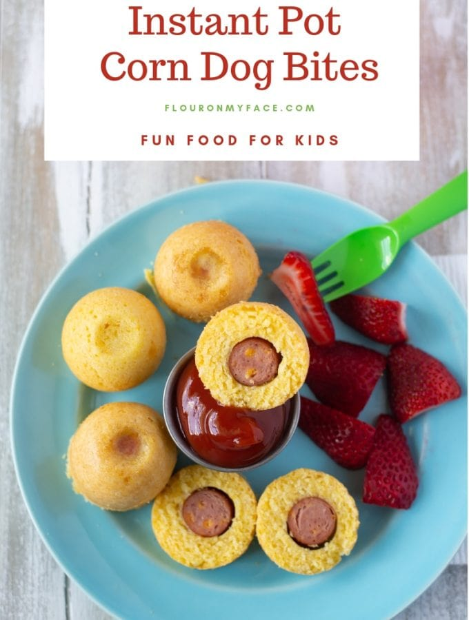 Instant Pot Corn Dog Bites served on a teal glass plate with a cup of ketchup and sliced strawberries for a summer time lunch.