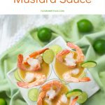3 mini plastic martini appetizer glasses filled with Key Lime Mustard Sauce and boiled pink shrimp on a green cloth napkin with fresh key limes