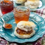A plate with a fresh biscuit with a thick spread of homemade Scuppernong Jelly with a jar of the jelly on a cloth napkin.