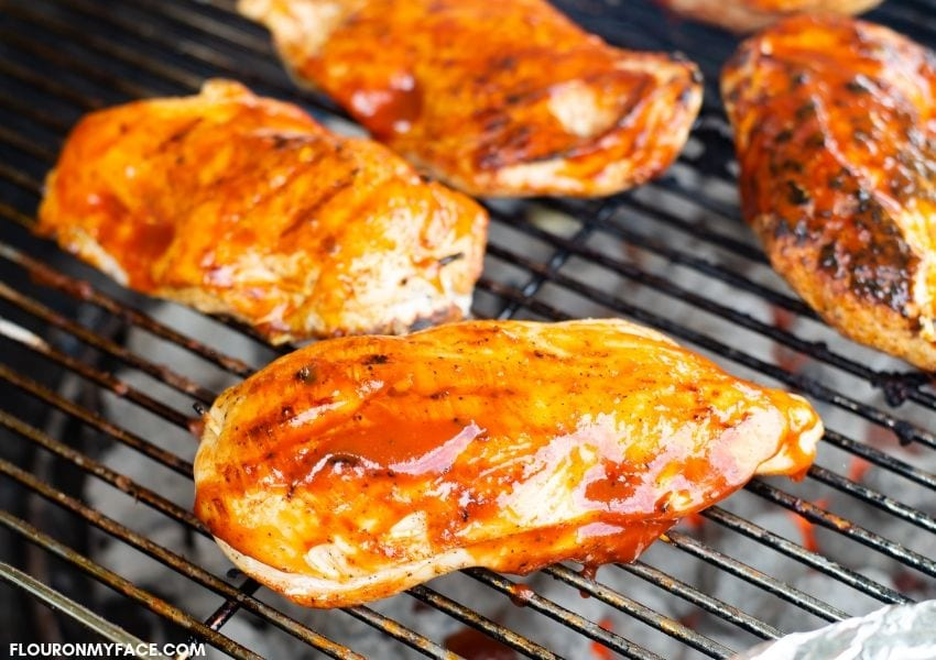 Spicy Jalapeno Popper Grilled Chicken slathered with barbecue sauce as it cooks on a charcoal grill