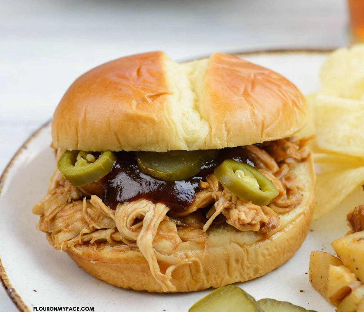 Close up photo of a barbecued chicken sandwich on a plate.