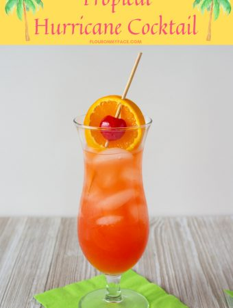 The Classic Hurricane Cocktail served in a tall hurricane glass with a orange slice and maraschino cherry garnish.