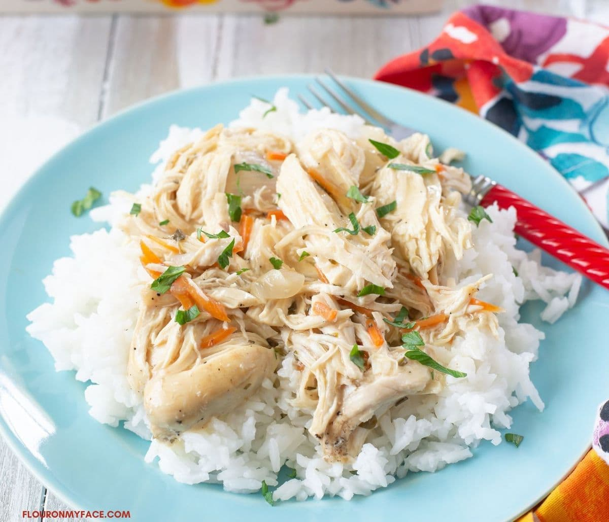Serving creamy herbed chicken over rice on a blue dinner plate.