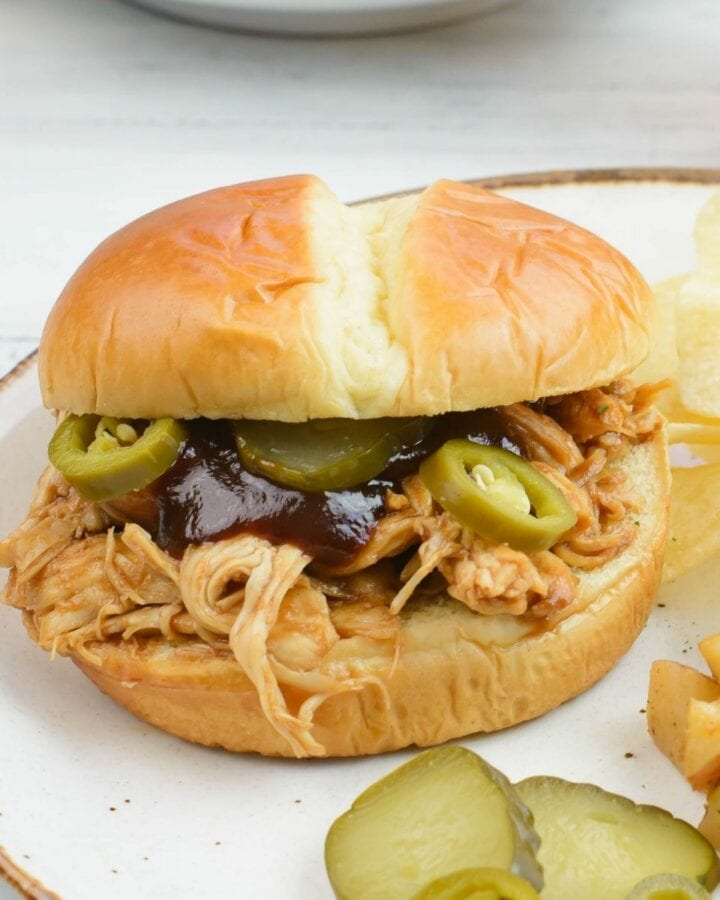 Crock Pot Pulled Chicken Sandwich with sliced pickles and jalapeno peppers on a bun.