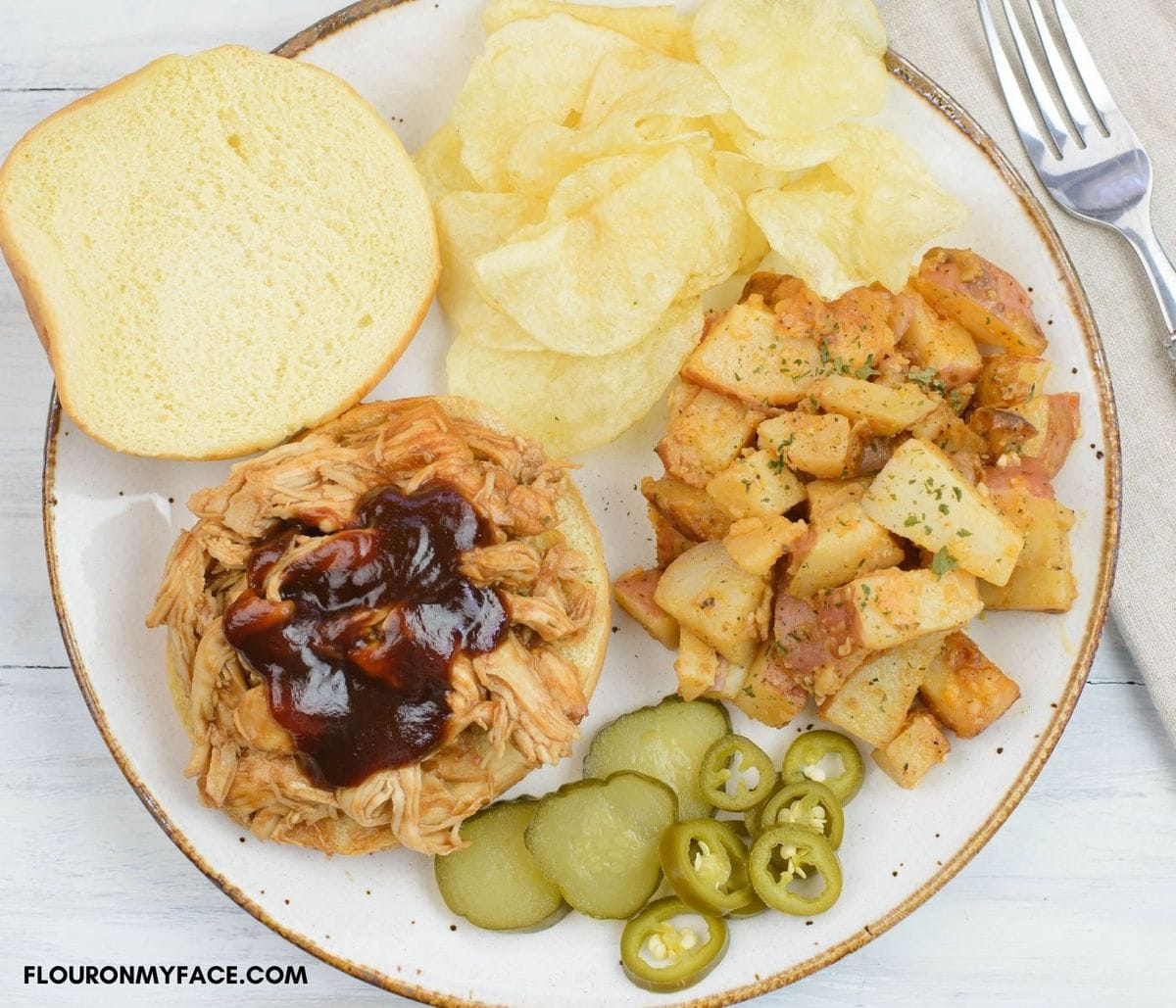 Opend pulled chicken sandwich with barbecue sauce, sides, chips, and slice pickles and jalapeno peppers on a dinner plate.