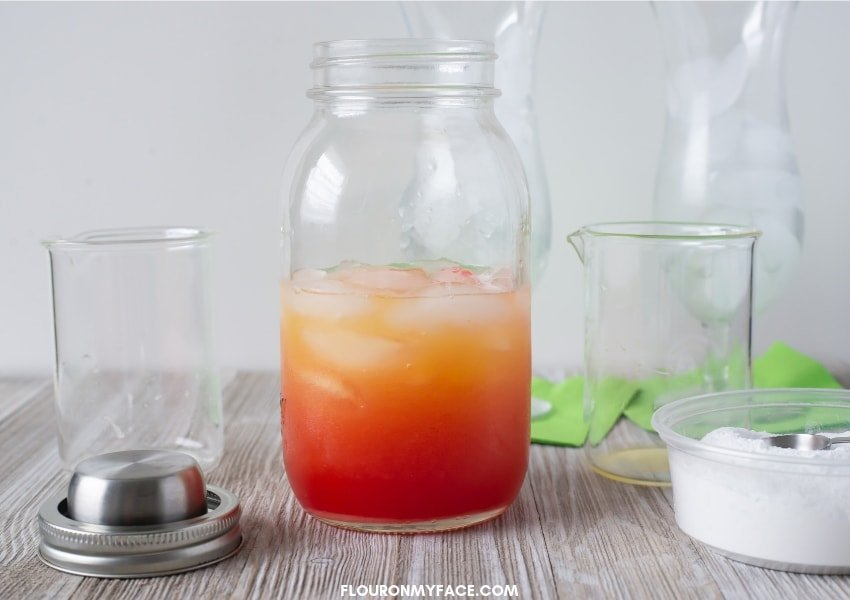 A photo of a Hurricane Cocktail ingredients in a clear mason jar cocktail shaker showing the layers of red and orange when the ingredients are combined before shaking.