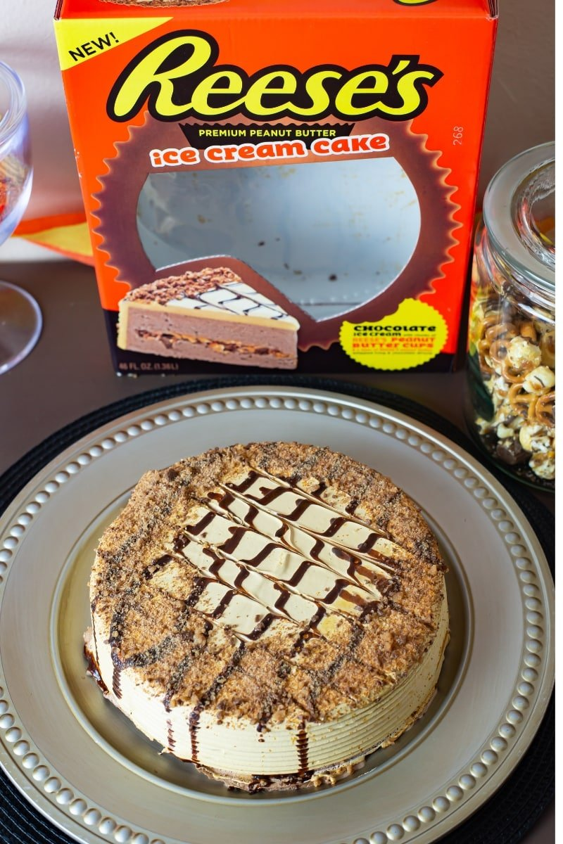 The new Reese's Ice Cream Cake on a serving platter with the box behind it on a party table.