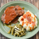 A green plate with 2 slices of Crock Pot Meatloaf covered in a tomato soup gravy with a side of mashed potatoes and green beans.