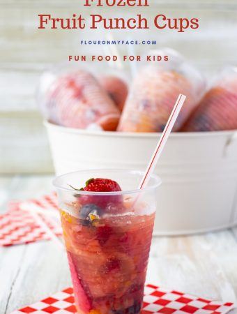 A clear plastic cup filled with fruit and punch then frozen. With a metal bucket in the background filled with ice and more Frozen Fruit Punch Cups chilling for a summer frozen treat. for the Fourth of July