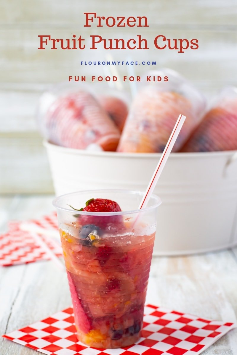 A clear plastic cup filled with fruit and punch then frozen. With a metal bucket in the background filled with ice and more Frozen Fruit Punch Cups chilling for a summer frozen treat.